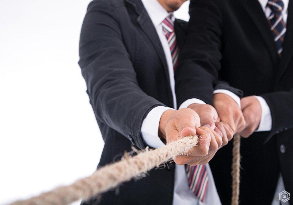 Homens de terno puxando uma corda