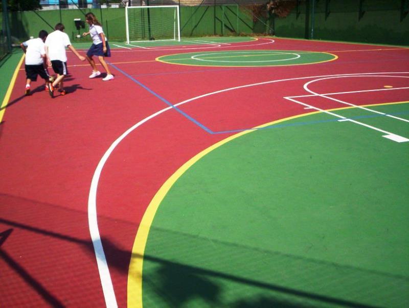 Foto - Quadra Poliesportiva - vermelha com verde nos recuos e áreas do goleiro